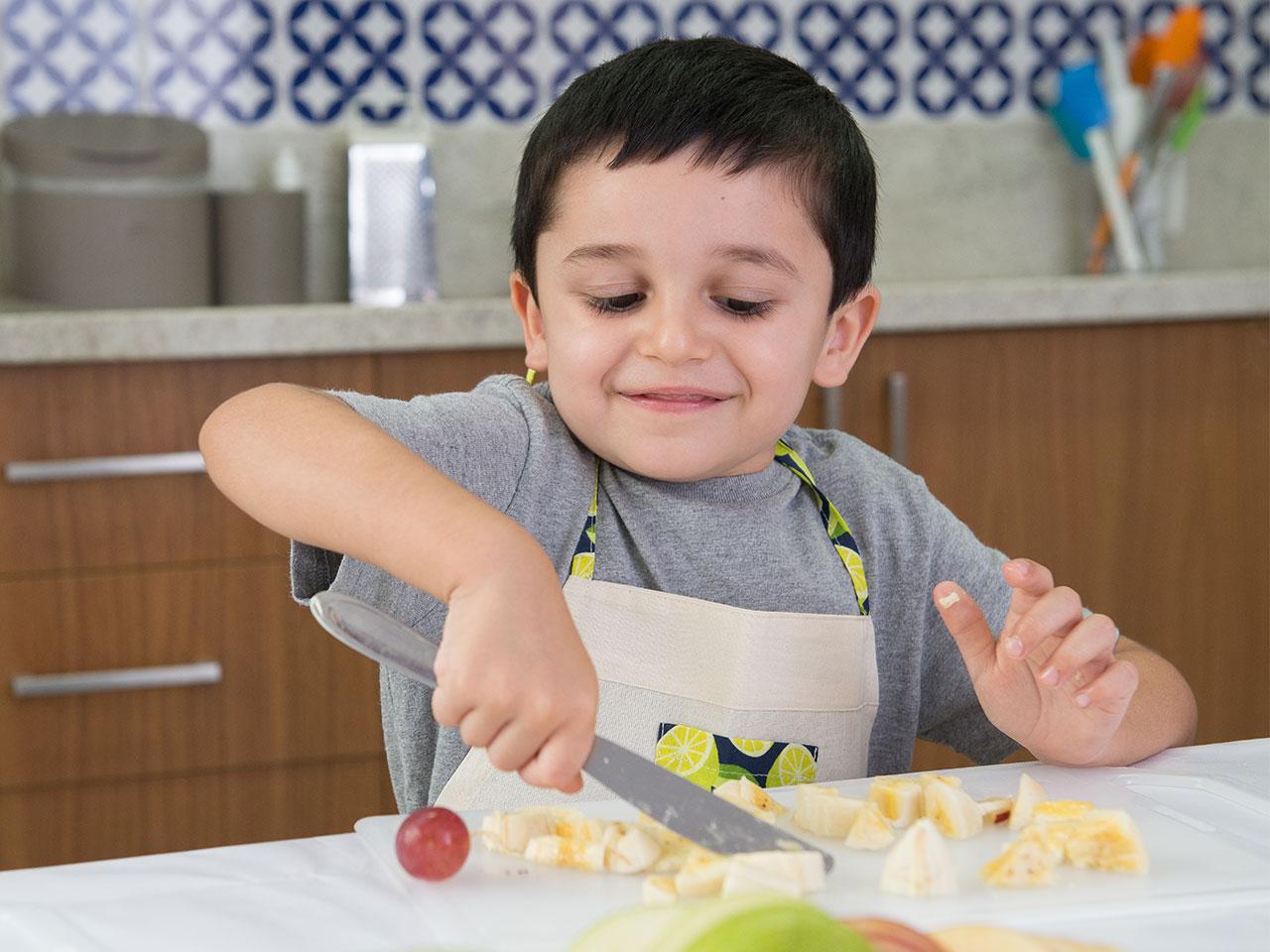 menino-cortando-frutas
